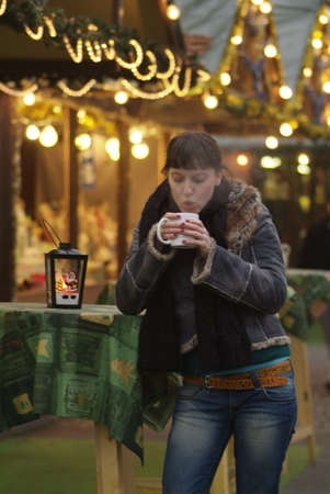 christkindlmarkt: a dark haired woman drinks glogg at the market stall