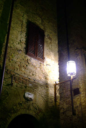 clinker tile: un latern en un brickswall durante la noche