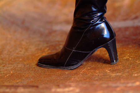 stilleto: Black boots with high heels on a brown floor Stock Photo