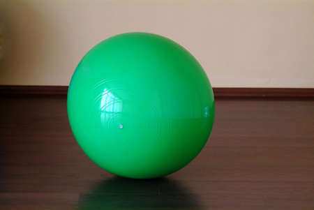 a green gym ball on the wooden floor
