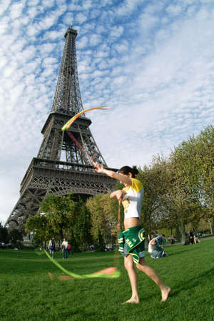 an acrobat in front of the eiffel tower