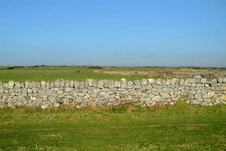 a small wall of stones on meadow