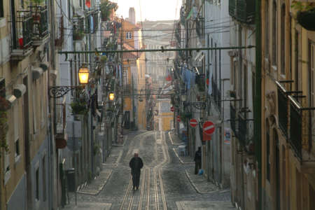 rails in front of row houses in lisbon photo