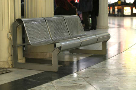 a bench of steel on an airport photo