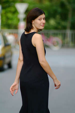 a  woman with a black dress takes a walk in the city