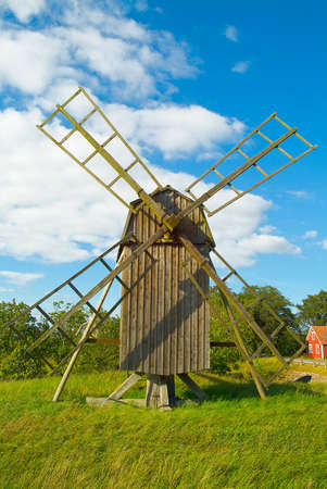 windmill on green gras and blue sky with white clouds photo