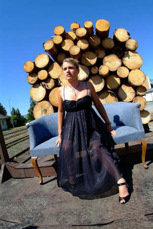blond women in black dress on a sofa in the backround boles and a blue sky