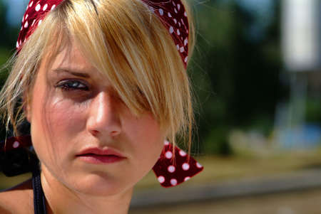 young blond women with a red cloth with white articles on it on her head Stock Photo