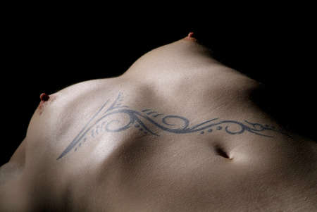 women upper part of the body with a black tattoo on it Stock Photo