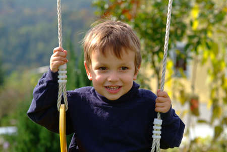 a little boy laughing on the swing