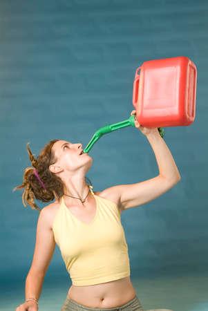 petrol can: una mujer joven de bebidas rojo gasolina puede
