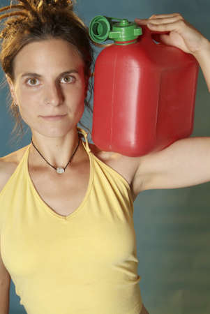 nonchalant: a young woman holds a red jerry can for petrol