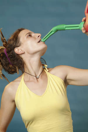 nonchalant: a young woman drinks from a red petrol can Stock Photo