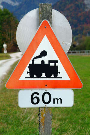traction engine: a traffic sign with attention train in sixty meter and meadow