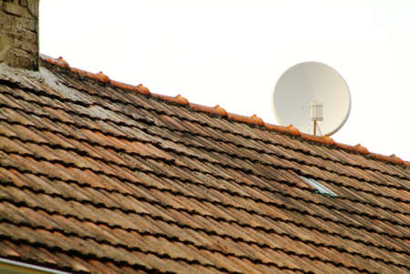 a white satellite dish fastens on the roof