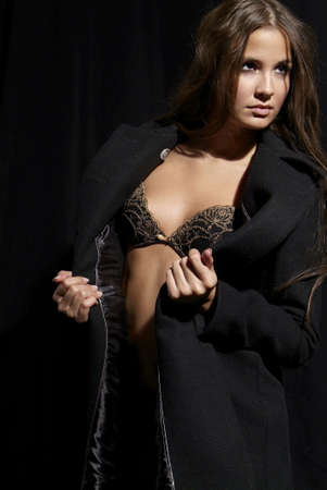 an erotic woman with bra and black overcoat