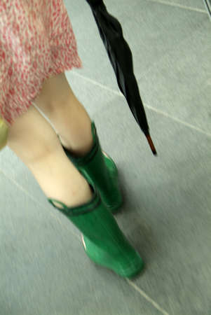 woman walks in short dress with green waterproof wellington boot and umbrella
