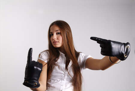 a standing woman shows her finger with leather gloves