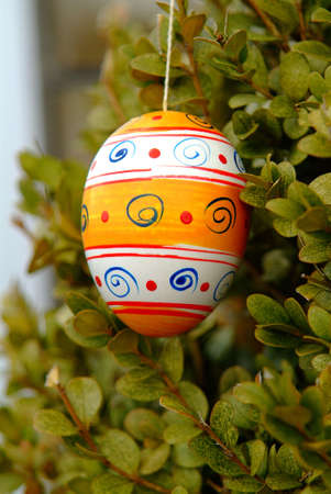 ornamentations: a coloured painted egg hangs on the bush