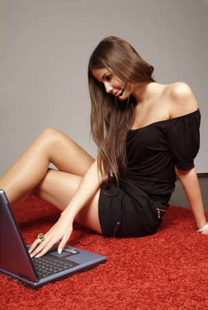 young friendly woman with black dress and laptop Stock Photo