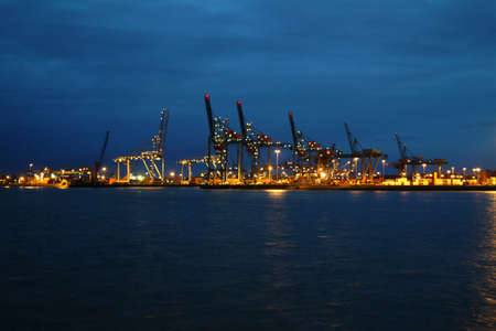 a lit port landscape at night with sea and crane in Rotterdam photo