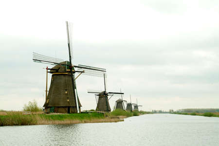 energy use: a river landscape with windmill and cloudy sky Stock Photo