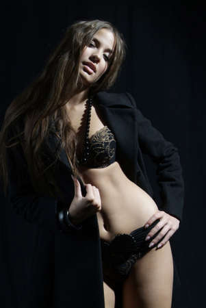 an attractive woman in the coat with underwear and necklet