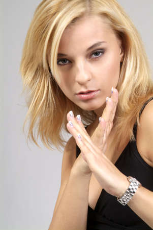 bluster: a cool blond woman with crossed hand