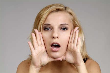 femme bouche ouverte: une jolie femme blonde avec la main et la bouche ouverte