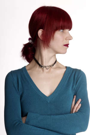 huffy: a serious woman with folded arm and red hair Stock Photo