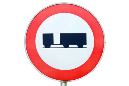 a ban on driving road sign for trucks with a trailer in the backround a wood photo