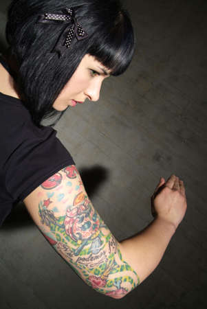 body consciousness: a woman with black hair and tattooed upper arm Stock Photo