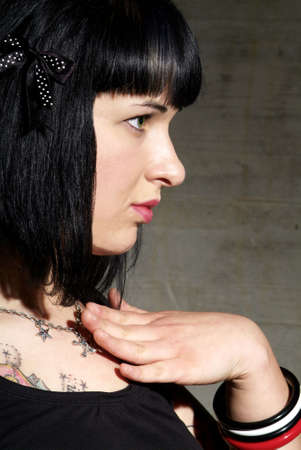 dactylology: a woman with black hair and tattoo Stock Photo