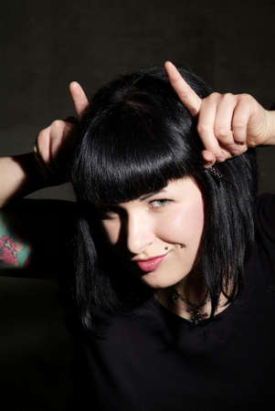 peruke: a woman with black hair and piercing shows horns