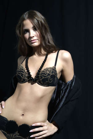 an attractive woman in the coat with bra and necklet