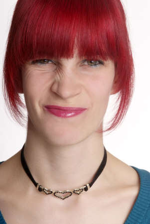 a young woman with red hair turns nose