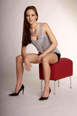 gorgios: woman with long hair and hot pant on red stool