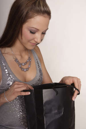 gorgios: sitting woman with long brown hair and black purchase bag Stock Photo