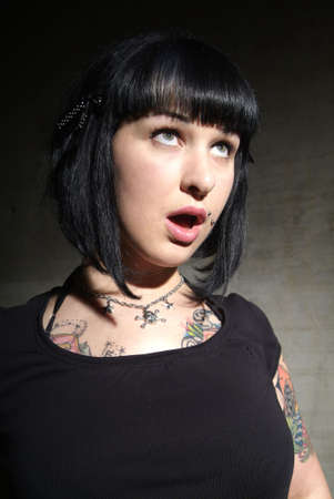 portrait of a young woman with tattoo and open mouth photo