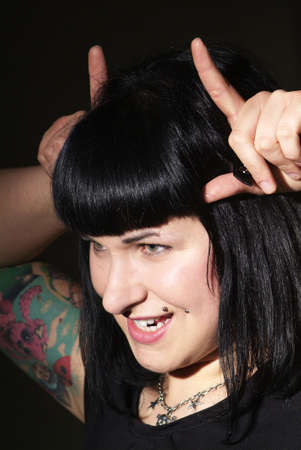 dangerouse: a woman with black hair and piercing shows horns