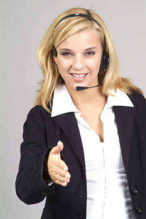 a friendly and motivated woman with headset and handshake photo