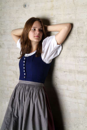 gorgios: a young woman with Dirndl leans at the wall