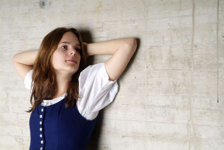 lean out: a young woman with Dirndl leans at the wall