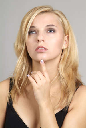 madam: a young blond woman holds her finger to the chin Stock Photo