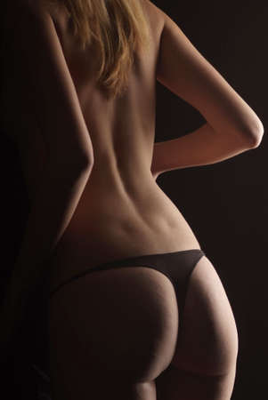 a young woman with tanga on black background