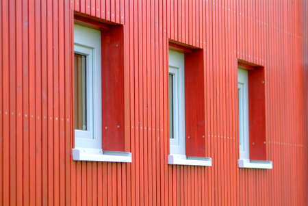three white windows in red batten house made of wood