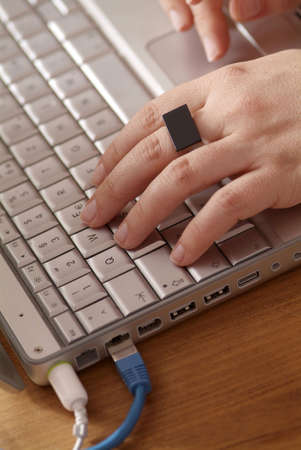 hands with black ring on keyboard of gray notebook Stock Photo - 3258830