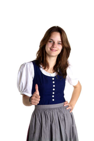 young woman in dirndl in front of white background shows thumb up