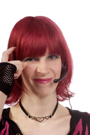 woman with red hair and headset scratching herself on head