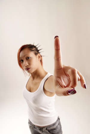 young woman holding up her index finger photo